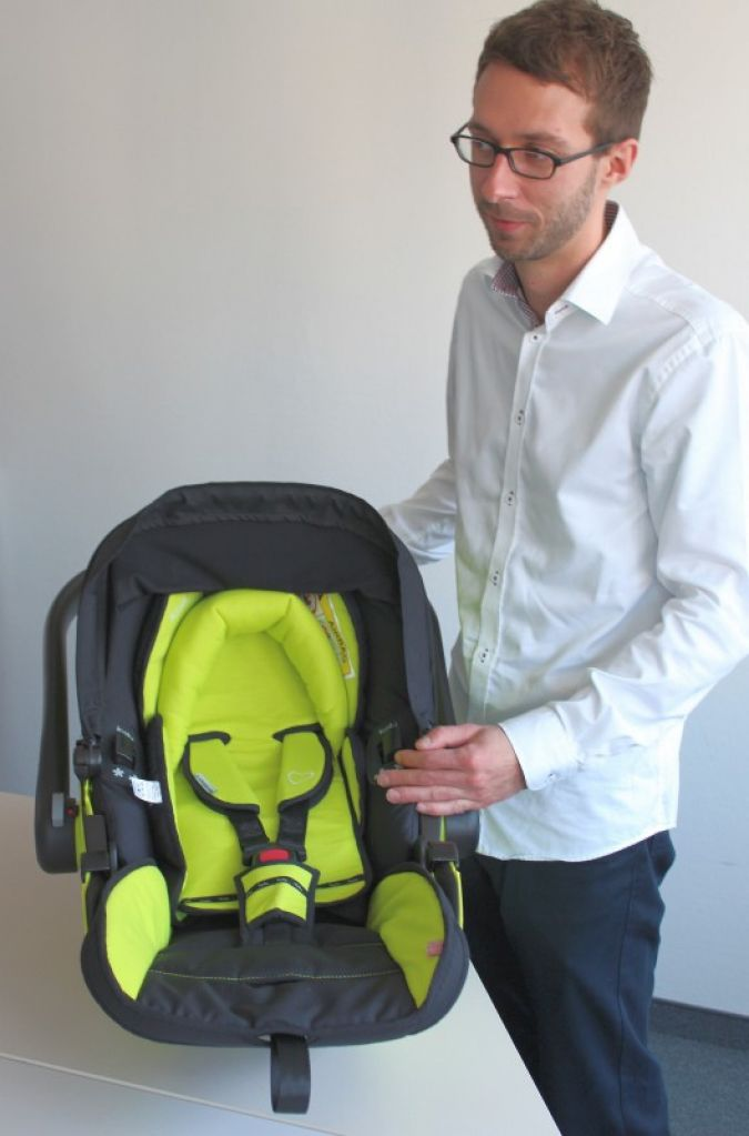 Christian Schneider, Marketing & PR Manager, zeigt der baby&junior Redaktion in Bamberg, was die neue kiddy-Babyschale alles kann.