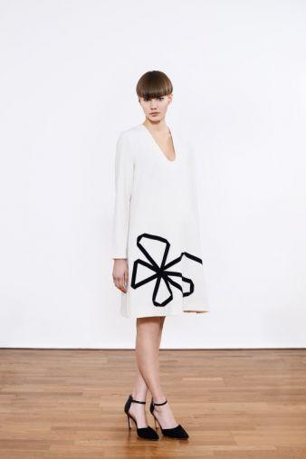 Ein Muss für die werdende Mama: das weiße Viskose-Kleid mit aufgenähter Blume aus schwarzen, elastischen Bändern.