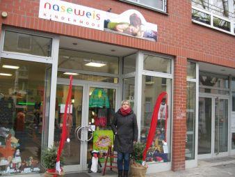 """Doris Petzold vor ihrem Laden """"Naseweis Kindermode"""", in dem eine Präsentationswand zeigt, wie Fashion für Kids angezogen aussieht."""