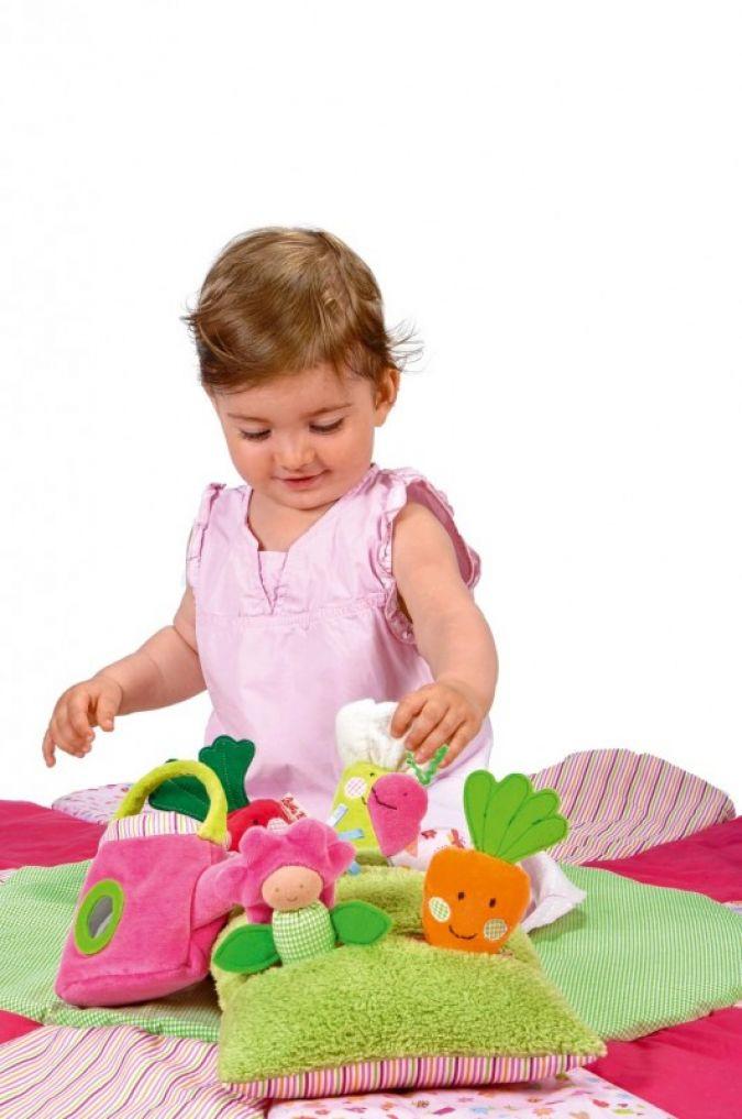 """Auf dem Spielkissen Wiese aus der Linie """"Im Garten"""" tummeln sich Radieschen, Karotte, Blume und Blumenkohl."""