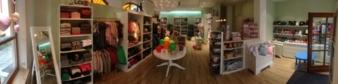 """Ein großer runder Tisch mit Luftballons oder anderen Dekos steht in der Mitte des Verkaufsraumes von """"Lotte Klamotte"""" in Ismaning bei München."""